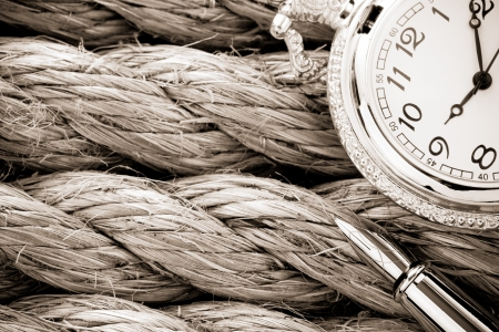 fixed line: pocket watch with ink pen on ship ropes Stock Photo