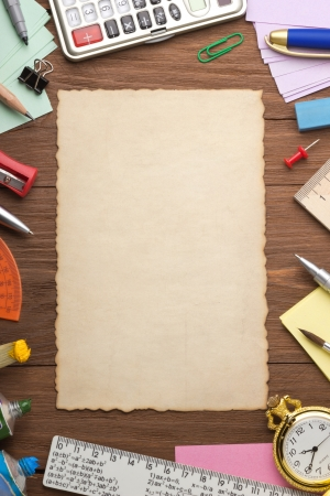 office supplies and aged paper on wood background photo