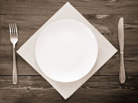 white plate, knife and fork at napkin on wooden background Stock Photo - 18200642
