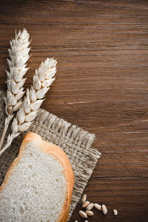 sliced bread and ears of wheat on burlap background photo