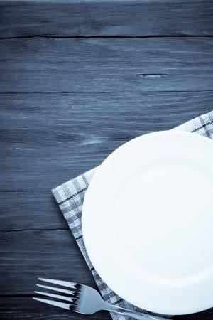cubiertos de plata: plato blanco y tenedor en la servilleta sobre fondo de madera