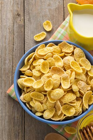 bowl of corn flakes  on wooden background photo
