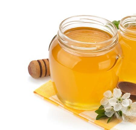 glazen pot vol met honing en stok ge Stockfoto