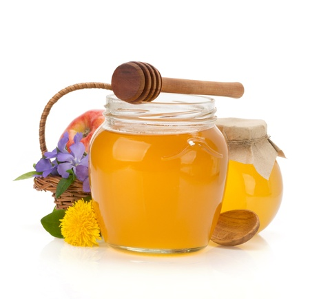 glass jar full of honey isolated on white background photo