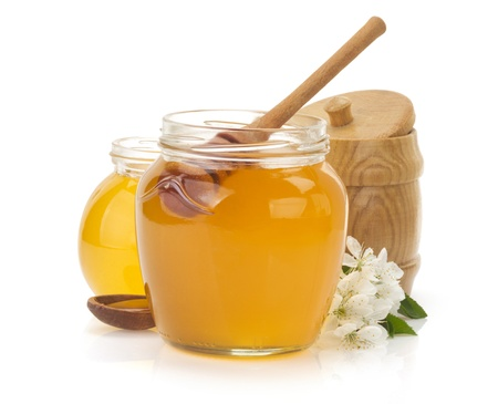 glass jar full of honey and stick isolated on white background photo