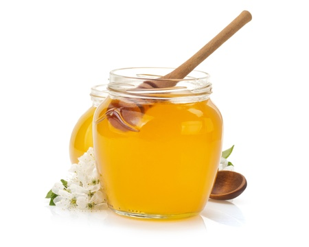 a jar stand: glass jar full of honey and stick isolated on white background