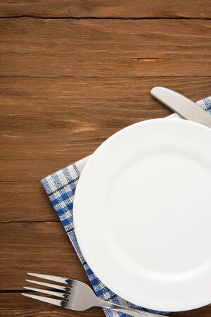 white plate, knife and fork at napkin on wooden background Stock Photo - 21229920
