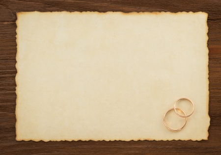 wedding ring and aged paper on wood background photo