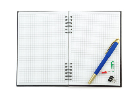 school supplies on checked notebook isolated at white background photo