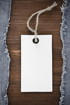 blue jean and price tag on wood texture background photo