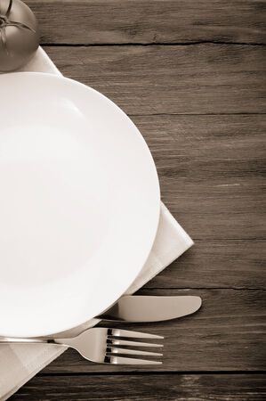grunge silverware: plate, knife and fork at napkin on wooden background
