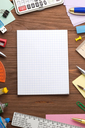 office supplies and checked notebook on wood background photo