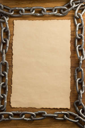 metal chain and old vintage ancient paper at wooden background photo