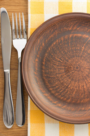plate, knife and fork at napkin on wooden background photo