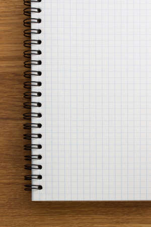checked notebook on wooden background photo