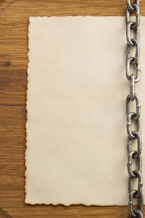 chain and old vintage ancient paper at wooden background photo