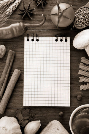 ear checked: notebook for cooking recipes and spices on wooden table Stock Photo