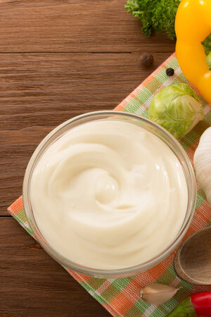 mayonnaise sauce in bowl on wooden background photo