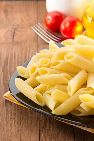 pasta Penne in plate on wooden background photo