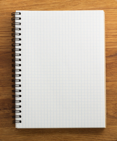 checked notebook on wood background photo