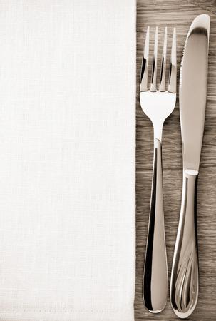 tovagliolo: coltello e forchetta al tovagliolo su sfondo di legno