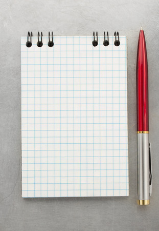 checked notebook at metal background texture photo