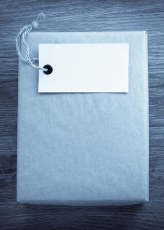 paper parcel wrapped tied with price tag on wooden background photo