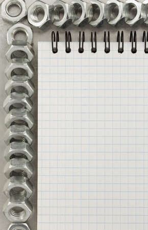 nuts tool and notebook at metal background photo