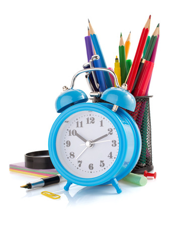 alarm clock and school supplies isolated on white background photo