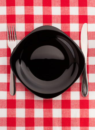 knife and fork at plate on napkin background photo