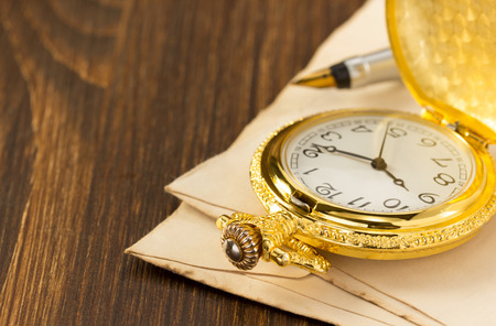 old envelope: watch and old envelope on wooden background Stock Photo