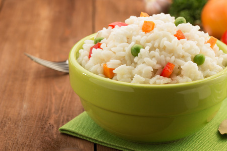 bowl full of rice isolated on wooden background