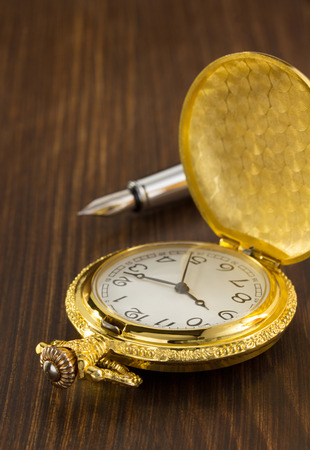 old pocket watch on wooden background photo