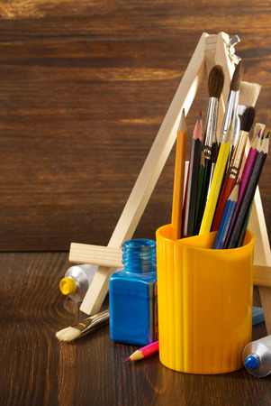 paint supplies on wooden background photo