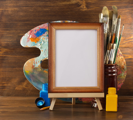 picture frame and paints on wooden background photo