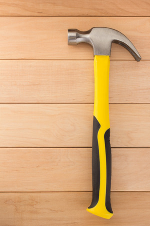 housebuilding: hammer tool on wooden background