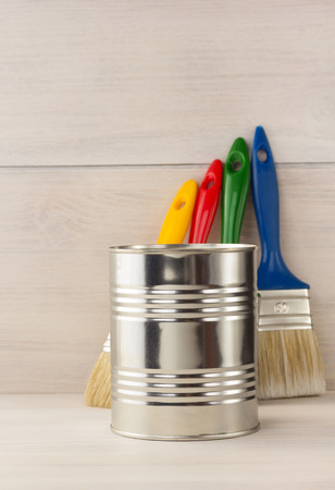paint bucket and paintbrush  on wooden background photo