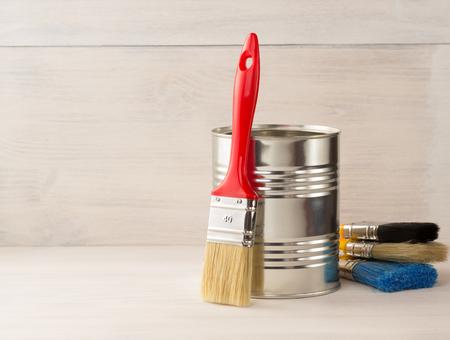 seau de peinture et le pinceau sur fond de bois Banque d'images