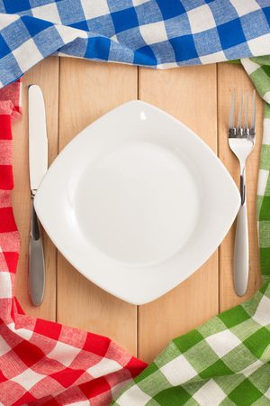 kitchen utensils and cloth napkin on wooden background photo