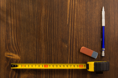 housebuilding: tape measure and pencil on wooden texture Stock Photo