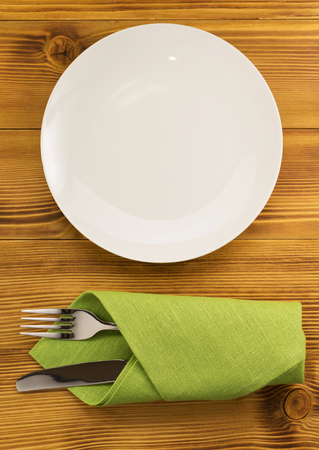 stainless background: knife and fork with napkin on wooden background