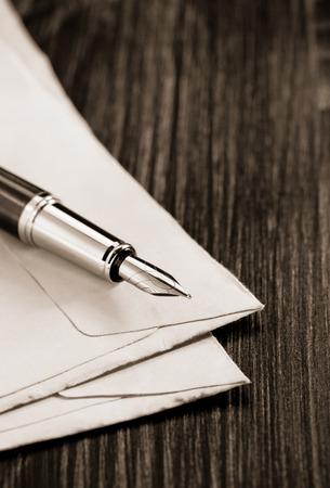old envelope: ink pen and old envelope on wooden background