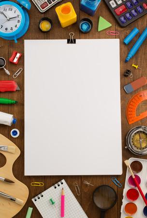 material escolar: útiles escolares y papel sobre fondo de madera