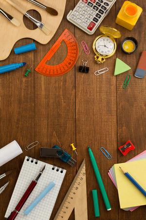 school supplies and notebook on wooden background photo
