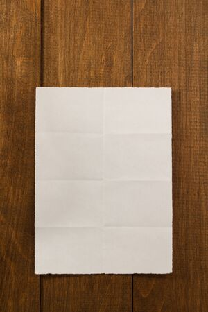 torn paper background: folded note paper on wooden background