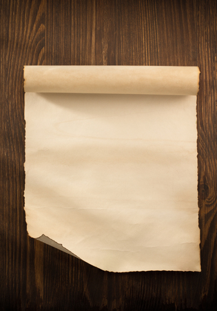 antique paper: parchment scroll on wooden background