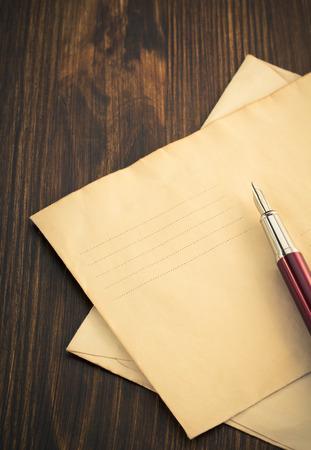 old envelope: old envelope and ink pen on wooden background