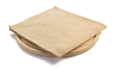 白い背景の上のまな板で袋黄麻布ナプキン 写真素材