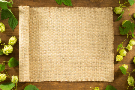 hessian bag: hop cones on wooden background Stock Photo