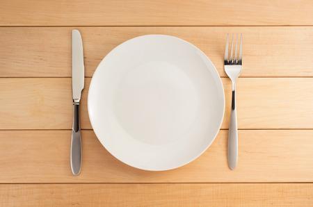 bord, mes en vork op houten achtergrond